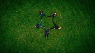 仰向けに寝た5人の足で作る星形