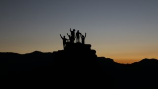 崖の上で手を挙げるグループ
