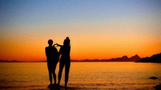 海辺にいる手先でハートを形作る男女