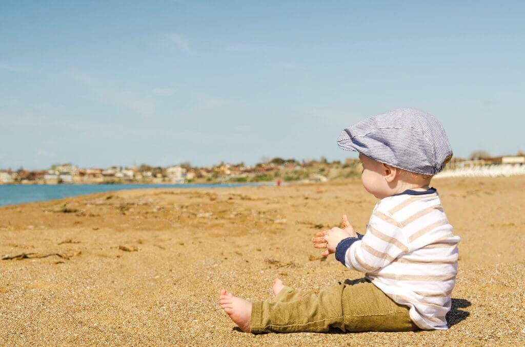 海辺に座っている幼子