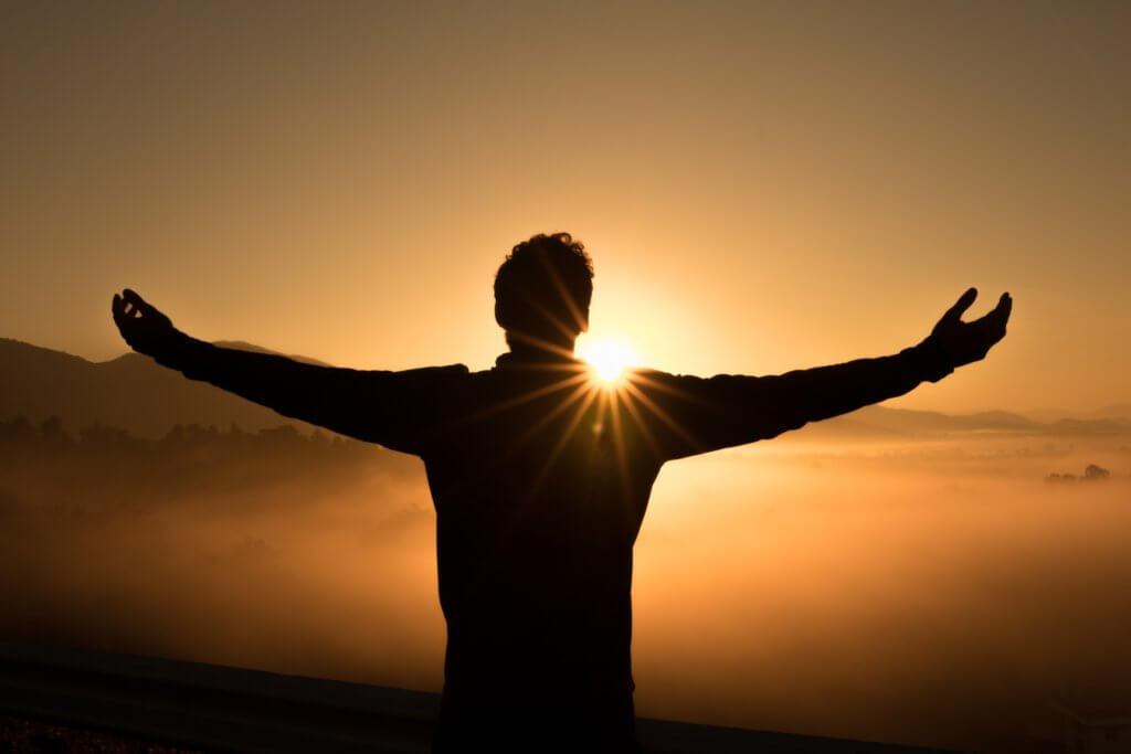 夕日に向かって手を広げる男性